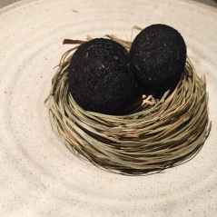 Small egg coated in ash, sauce made from dried trout and pickled marigold, Fäviken Magasinet, Sweden